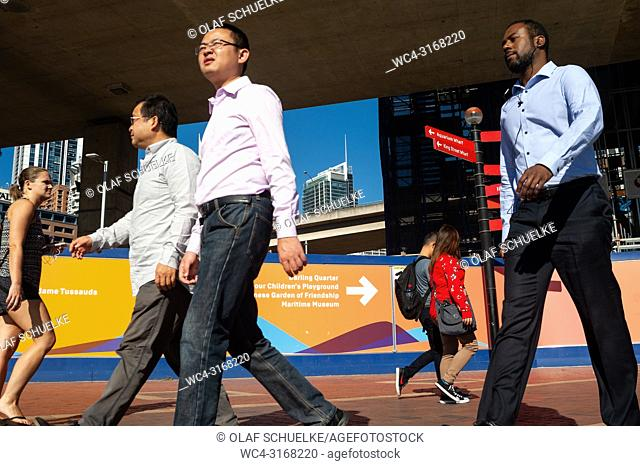 Pedestrians walk along the waterfront at Cockle Bay in Darling Harbour. Sydney, New South Wales, Australia