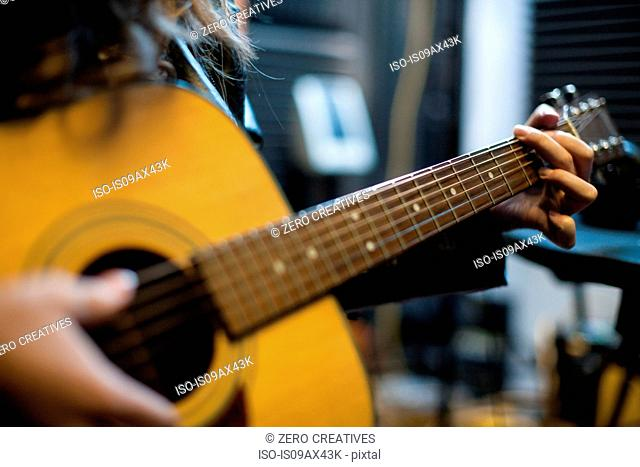 Young woman playing guitar, mid section, close-up