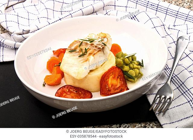 grilled cod with mashed potato, carrots, slice tomato and mushy pea