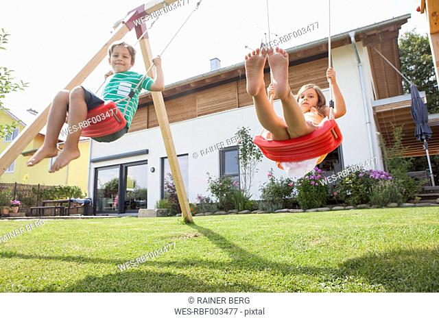 Brother and sister on a swing in garden