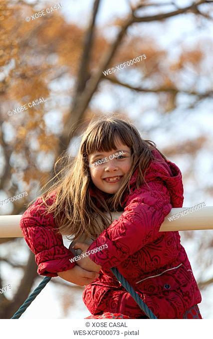 Portrait of smiling little girl climbing on playground equipment