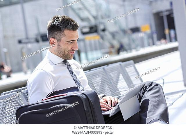 Businessman using digital tablet at waiting area