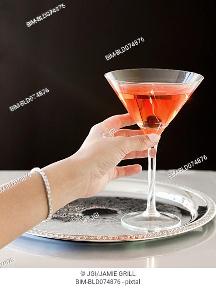 Woman reaching for martini on tray