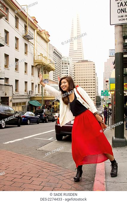 A woman on the side of the road hailing a cab, san francisco california united states of america