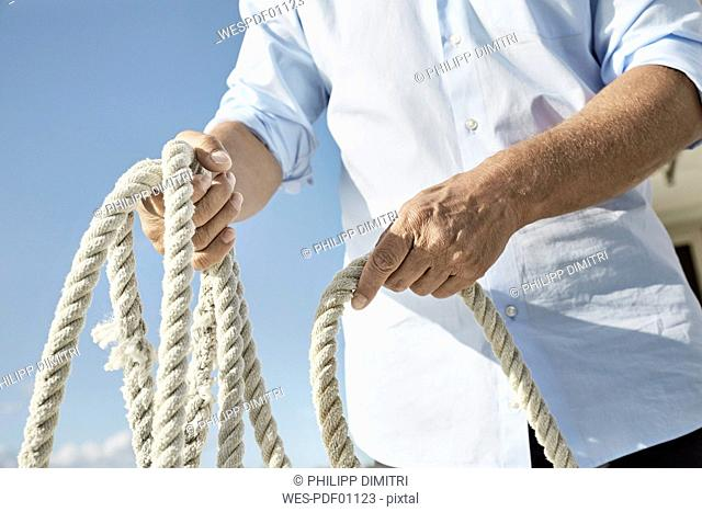 Mature man holding rope on motor yacht, partial view