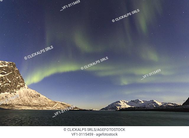 The Northern Lights and moon are reflected in the cold sea in the polar night Lyngen Alps Tromsø,Norway Europe