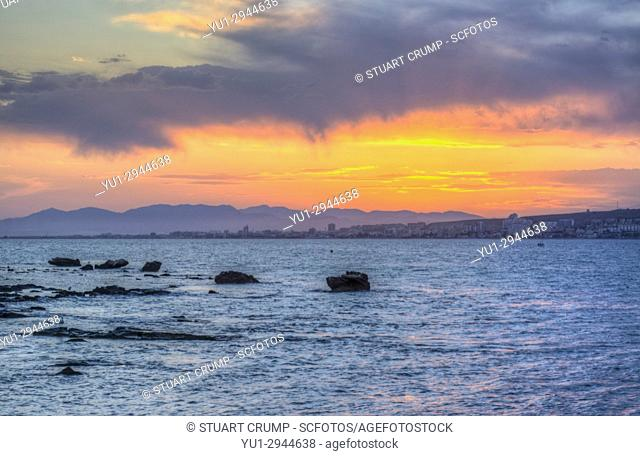 HDR image of a sunset over rocks in the sea on the Spanish island of Tabarca