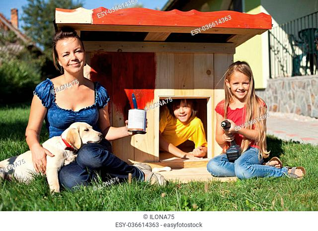 Happy kids painting the doghouse to shelter their new labrador puppy