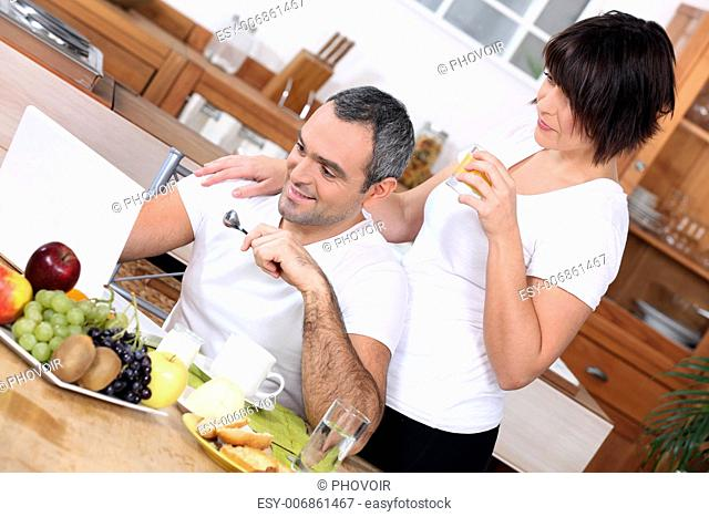 couple having breakfast and looking a computer
