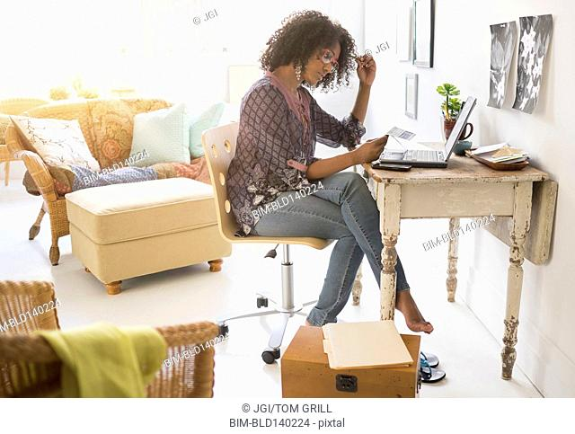 Mixed race woman using laptop in living room