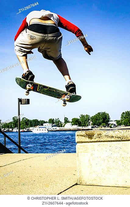 Teenage boy practices his jumps and tricks on a skateboard at the park in Port Huron Michigan