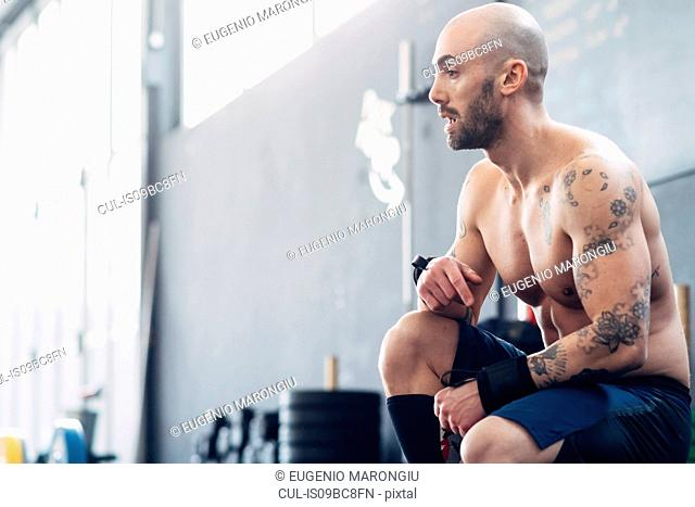 Portrait of tattooed man in gym looking away
