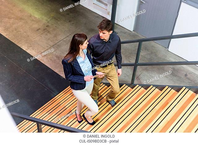 Two colleagues in industrial building, walking up stairs, in conversation, elevated view