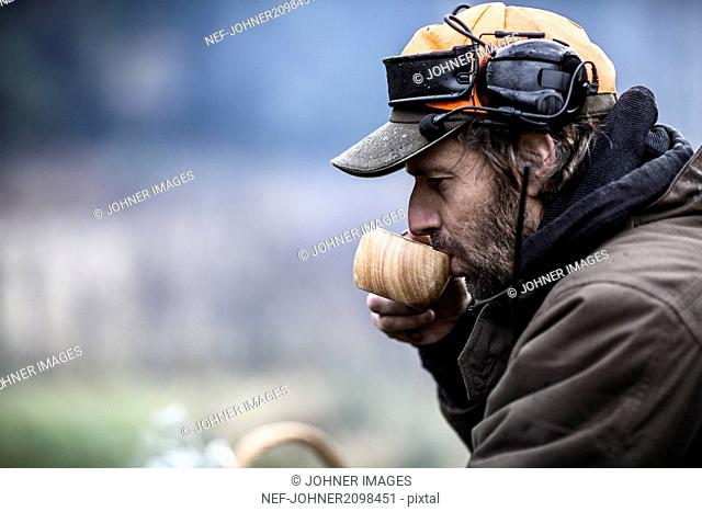 Hunter drinking from wooden cup