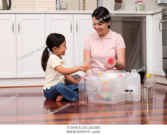 Mixed Race mother and daughter filling recycling bin