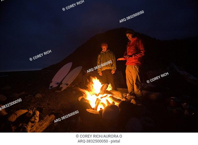 Two men stand around a camp fire on The Lost Coast, California