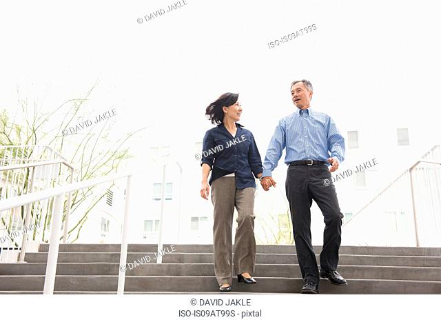 Low angle full length front view of mature couple holding hands descending stairs