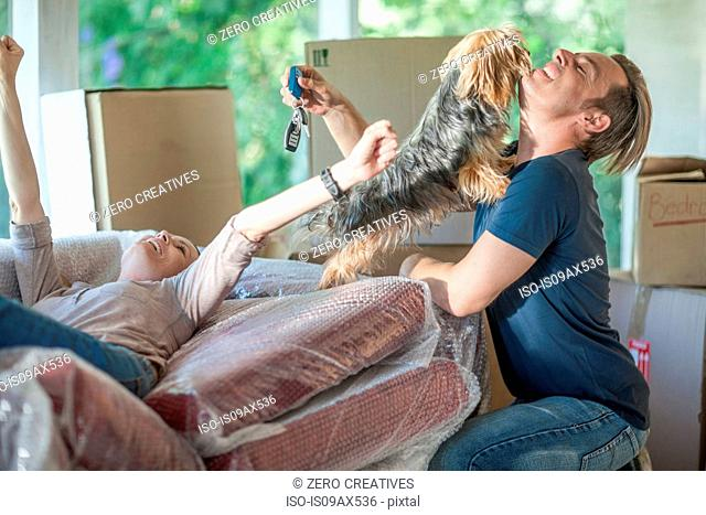 Moving house: man holding house keys, woman relaxing on bubbled wrapped sofa and dog jumping up at man