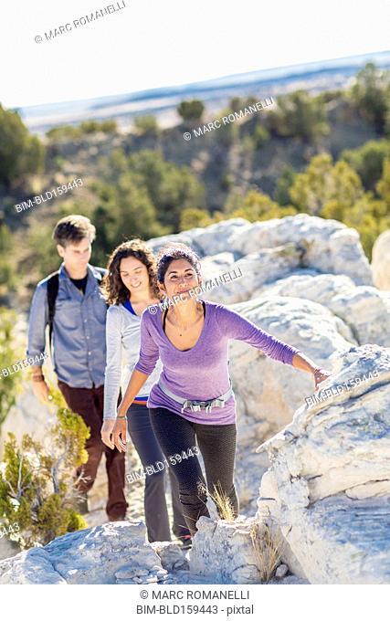 Hikers climbing rocky hillside