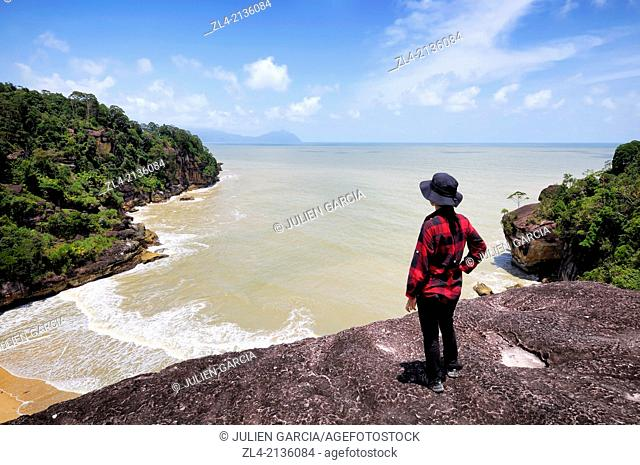 Woman watching the South China sea from a lookout on the Telok Pandan Kecil trail. Malaysia, Borneo, Sarawak, Bako National Park. Model Released