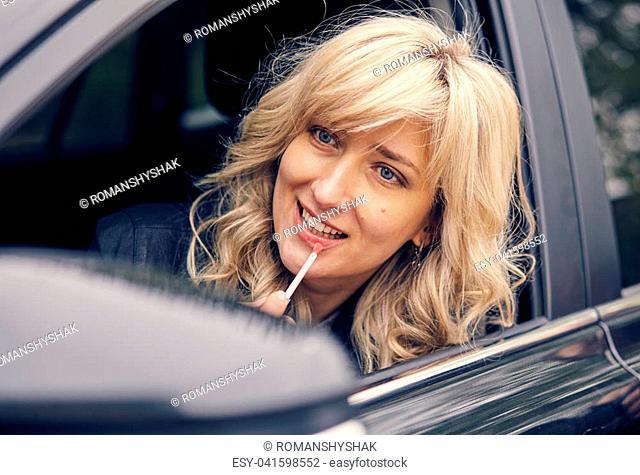 A beautiful woman in the car window draws her lips