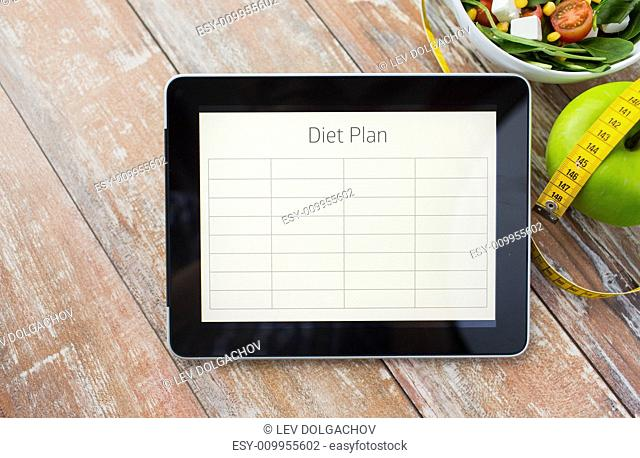 healthy eating, dieting and weigh loss concept - close up of diet plan on tablet pc screen, green apple, measuring tape and salad