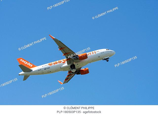 Airbus A320-214 WL, commercial passenger twin-engine jet airliner from British low-cost carrier airline EasyJet in flight against blue sky