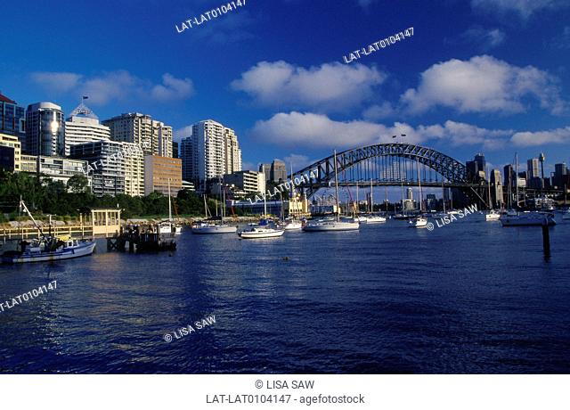 Sydney Harbour bridge. Curved steel. Lavendar Bay. Houses,tall buildings on water. Boats