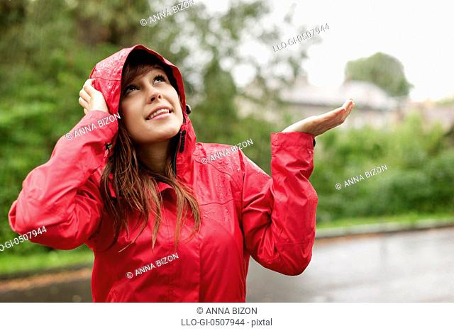 Beautiful woman in raincoat checking for rain, Debica, Poland