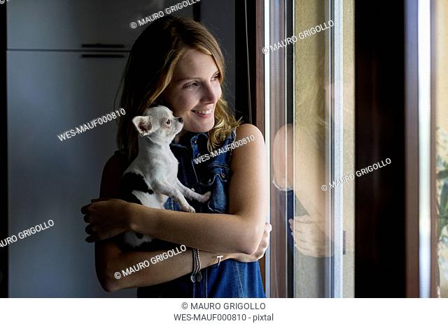 Smiling woman with dog on her arms looking through window