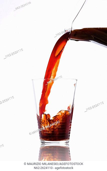 Drink poured from a jug into a glass on white background