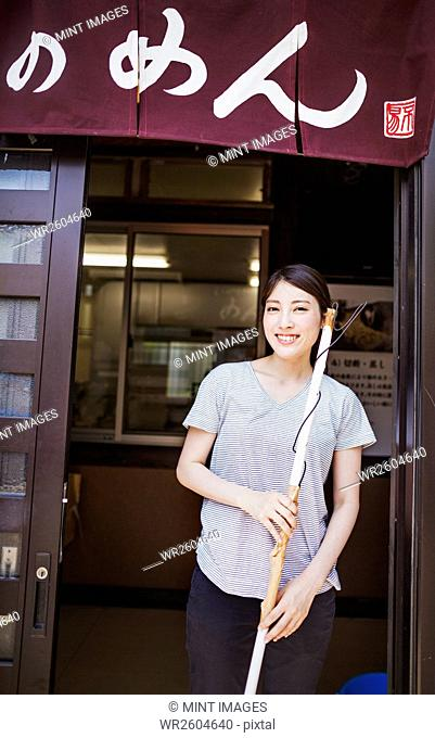 Woman standing by the door of a small noodle shop with a brush