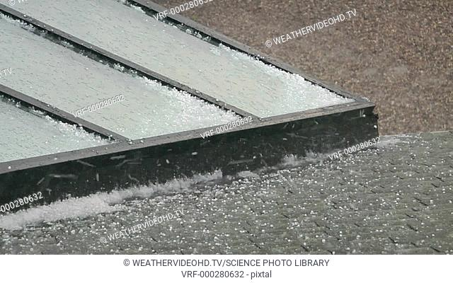 Pea-sized hailstones accumulating in drifts on a roof. Filmed in the USA on a spring afternoon