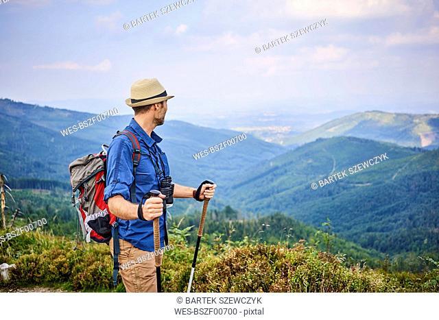 Man admiring the mountain view during hiking trip