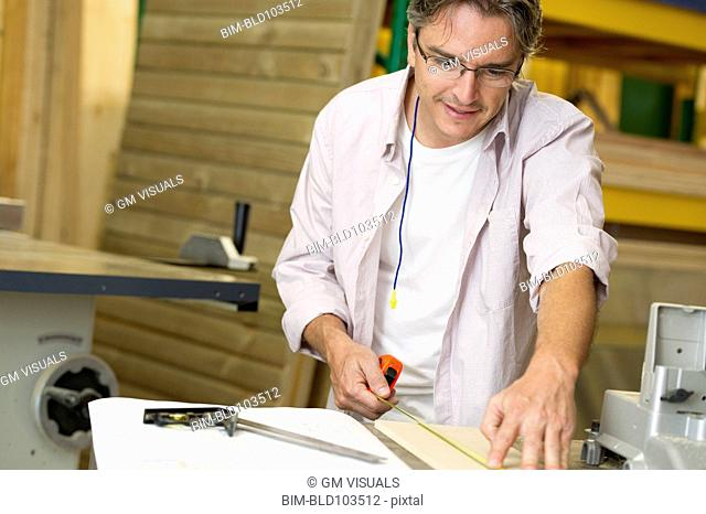 Hispanic carpenter measuring wood in workshop