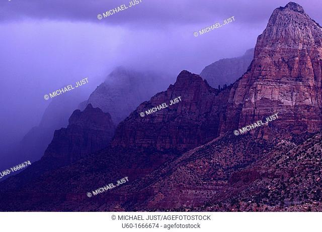Dark and menacing storm clouds move across the canyon walls at Zion Canyon at Zion National Park, Utah