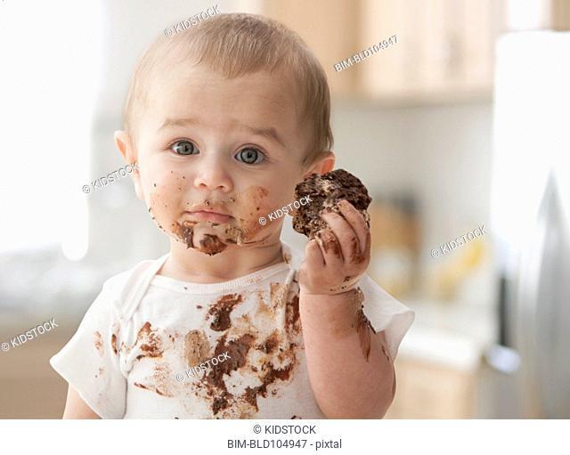 Messy Hispanic baby eating cake