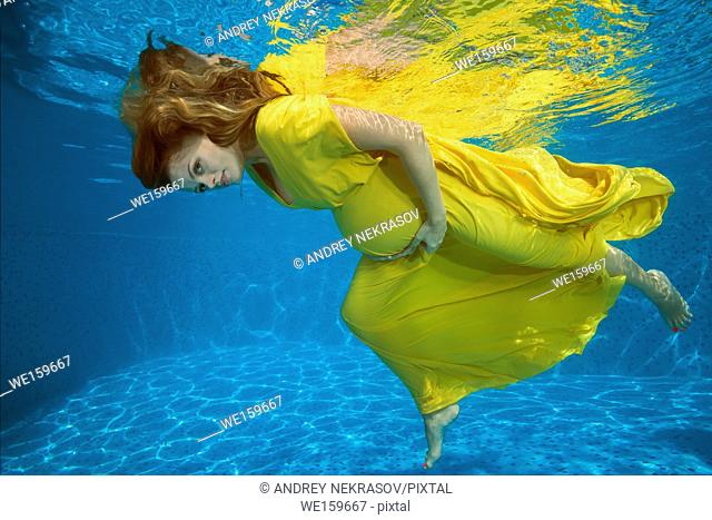 Young pregnant woman in yelow dress under water in the pool