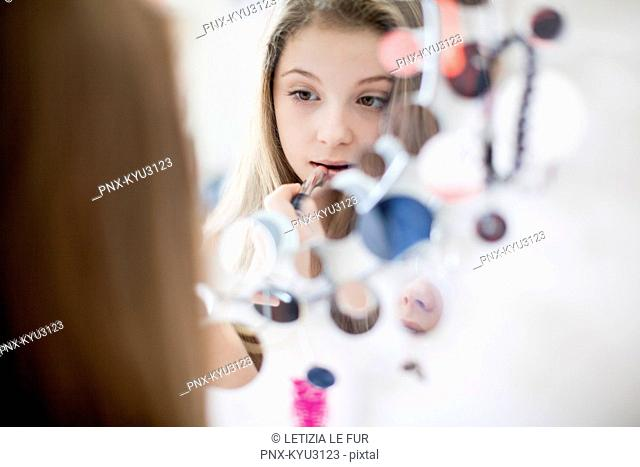 Girl applying lipstick on mirror