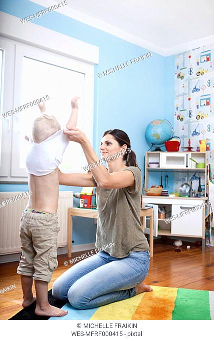 Woman undressing his little son at children's room