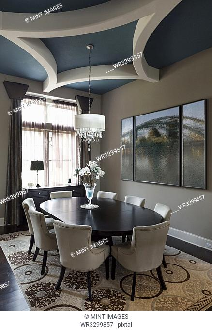 Table and chairs with paintings in dining room