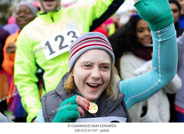 Enthusiastic woman with medal cheering at charity race