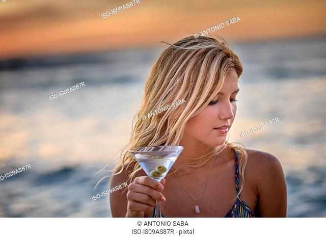 Young woman drinking cocktail on beach at sunset