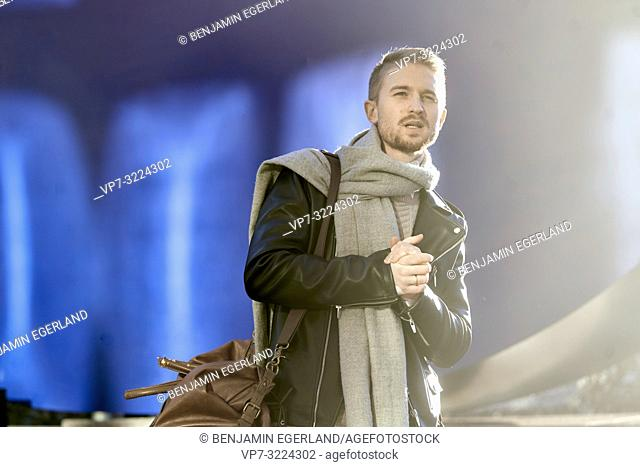 confident young man wearing stylish winter clothes, men's fashion, in Munich, Germany