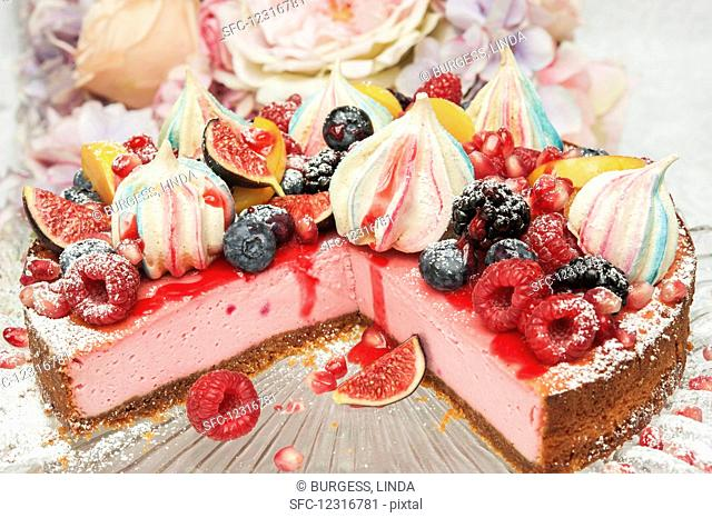 Strawberry cheesecake with merangue kisses and fresh fruit on the top on a glass cake stand in front of flowers