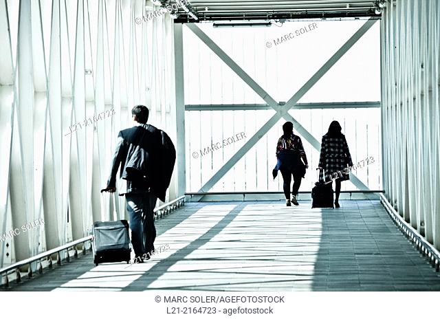 Travellers, men, women, with their backpacks and suitcases wheels on a catwalk, gangway. Airport, El Prat de Llobregat, Barcelona, Catalonia, Spain