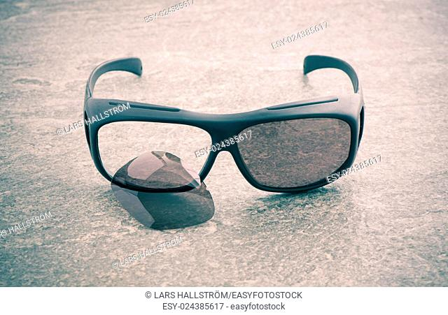 Broken sunglasses on stone table. Shades with one glass missing