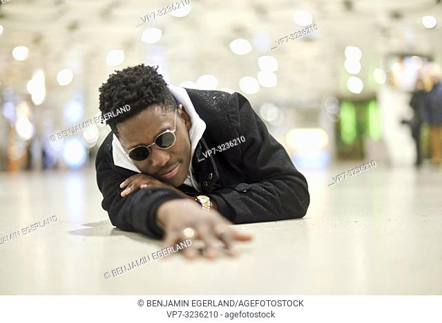 young man laying on the ground in public, in city Munich, Germany