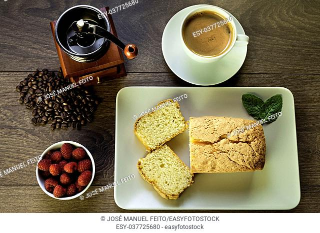 sponge cake, raspberries, cup of coffee, coffee beans and coffee grinder on wood