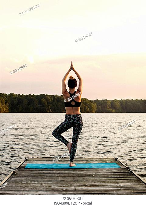 Rear view of woman on pier by lake standing on one leg in yoga position, North Carolina, USA